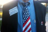 Election Judge James White shows off his patriotic neckware while working the polling place early Tuesday at Aikin Elementary on Pleasant Valley Road in northeast Dallas.(Louis DeLuca)