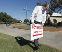 Election Clerk Warren Tyson posts polling place signs Tuesday morning outside the Euless Public Library.(Michael Ainsworth)