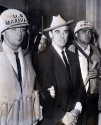 U.S. marshals escorted Walker after his arrest on the Ole Miss campus on Oct. 1, 1962. On his head was a hat he'd been given as a welcome gift by Dallas Mayor Earle Cabell.