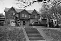Walker flew U.S. flags upside down outside his Dallas home in 1963. He was inside that April when Oswald took a shot at him. The bullet was deflected as it struck the frame between windowpanes, and Walker was only hit by fragments.