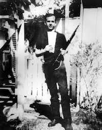 Lee Harvey Oswald posed with a rifle in the backyard of his Oak Cliff apartment in 1963.