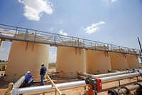 Pipeline technician Jeremy Wagner  talks with gang pusher Ruben Duran next to the holding tanks of used drilling water on land owned by Fasken Oil and Ranch. Recycling water might work out to be more expensive than buying fresh water, but not by much, the head of Fasken's oil and gas operations says.(Vernon Bryant - Staff Photographer)