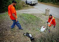 Samuel Corley (left) and Cornelius Alfred  install a digital water meter at a home in Cedar Hill. The new meters can send information in real time to the city's utility billing department, and customers will be able to go online and check their water usage.(G.J. McCarthy - Staff Photographer)