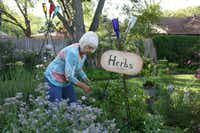 Arlene Hamilton demonstrates some of the selections in the edible island of her Waxahachie garden.