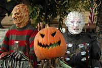 Figures based on horror movie characters Freddy Krueger (left) and Pinhead stand behind a jack-o-lantern at the home of Ralph Granado.