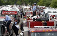 Firefighters and trucks gather in a staging area Thursday in West before a procession to Waco's Ferrell Center for a memorial honoring victims of last week's deadly fertilizer explosion.