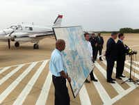 County Judge Clay Jenkins and Mayor Mike Rawlings spoke near a Beechcraft aircraft that will be used to spray pesticide in Dallas County.