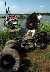 Jeremy Carter piles up old tires dredged from the bottom of White Rock Lake near Sunset Bay, on the eastern side of the lake, in June 1999.
