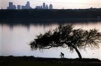 A lone cyclist rides around White Rock Lake in Noember 1999. The city built the cycling and jogging path around the lake in 1976.