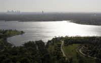 The Dallas skyline is visible in the distance in this aerial view from the north side of the lake in March 2010. The lake was formed by damming White Rock Creek, which today widens into the lake before continuing south out of the spillway and emptying into the Trinity River. The lake covers 1,254 acres in East Dallas.