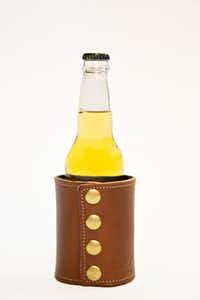 Coozie from Whitewing has neoprene liner that is sewed on the inside of the leather in order to insulate as well as keep cans and bottles from sweating on and through the leather. The snaps on the side were added for style as well as easy breakdown to flatten out for travel. $40.