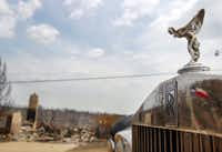 The hood ornament of a Rolls-Royce overlooks the devastation on Hells Gate Loop in the Sportsman's World area near Possum Kingdom Lake. The car, perched atop a trailer, survived the wildfire that destroyed surrounding homes.