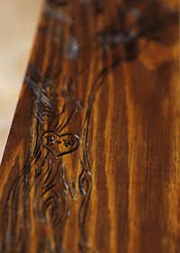 Her detailed designs are burned into the wood.