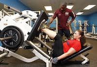 Fitness instructor Floyd Williams, standing, of fitness ministry of Oak Cliff Bible Fellowship, assists church member Heather Gregory.