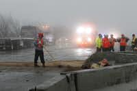 Workers cleaned up debris and fuel spills in the fog on eastbound I-30 early Friday.