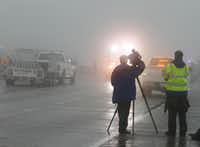 A local TV reporter and photographer work in the fog after an accident early Friday morning closed both sides of I-30.