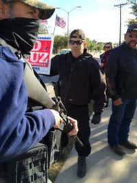 David Wright (center) organized the protest and brought his tactical shotgun