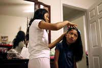 In a morning mother-daughter ritual,   Aidelin Méndez brings hair bows to her mother, Yolanda Méndez, who places them in the girl's long hair. This day was special -- it was Aidelin's first day of school.